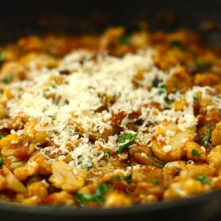 A healthy, hearty, and delicious vegan-friendly dish featuring cauliflower, raisins, olives, parsley, and walnuts baked in a simmering tomato sauce.